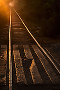 Rail road tracks fading off into sunrise at crossing, Monywa