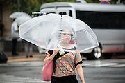 Lady walking under the rain. Typhoon number 10 called Lionrock hit japan early on morning, in Tokyo. 30/08/2016-Tokyo, JAPAN