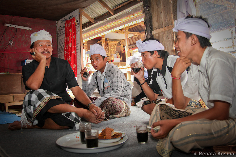 Young Balinese men sit down to enjoy coffee and snack during gathering at Ulun Danu Batur temple. This pura is an important social and religious center of the area.