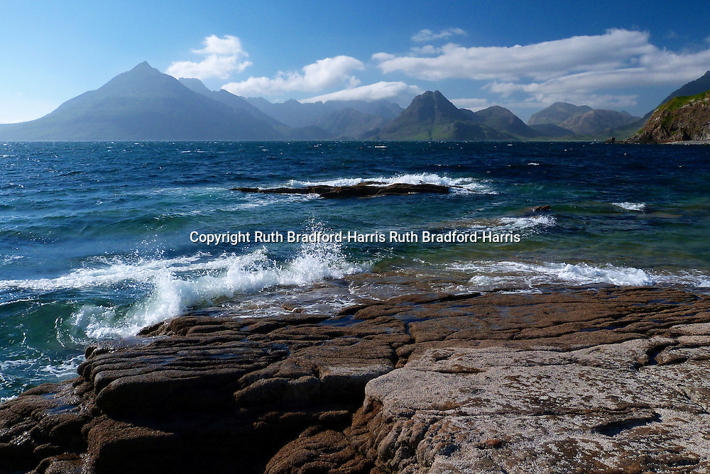 The violet-hued Black Cuillin from the Limestone pavement at Port Elgol, Isle of Skye. The prominent Gabbro peaks are Gars-bheinn at far left, Sgurr na Stri right of centre and Marsco in the right distance,  which marks the start of the Granite mountains referred to as the Red Cuillin.<br /> <br /> Waves are breaking onto the  Limestone pavement which dips into and under the sea in the direction of the Cuillin, looking like a natural landing stage.<br /> <br /> Limestone is rare on the island, occurring only in a band from Broadford to Elgol via Strath Suardal. At Torrin, the Limestone was altered by metamorphism caused by the later intrusion of plutonic Granite into the famous Skye Marble.<br /> <br /> Date taken: 17 June 2016