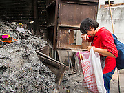 "10 AUGUST 2014 - BANGKOK, THAILAND:     A woman shields her eyes while throwing joss paper into an incinerator on the first day of Ghost Month at Wat Mangkon Kamalawat, the largest Mahayana Buddhist temple in Bangkok's Chinatown. The seventh month of the Chinese Lunar calendar is called ""Ghost Month"" during which ghosts and spirits, including those of the deceased ancestors, come out from the lower realm. It is common for Chinese people to make merit during the month by burning ""hell money"" and presenting food to the ghosts.PHOTO BY JACK KURTZ"