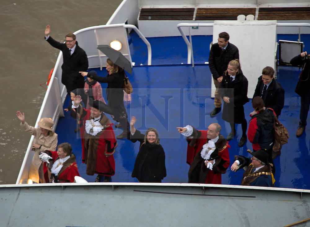 © Licensed to London News Pictures. 14/11/2015.  The brand new Lord Mayor of London has travelled down the Thames this morning as part of a 40 boat flotilla. The new Lord Mayor Jeffrey Evans​ was due to be on board the Queen's row barge Gloriana but due to wet weather conditions he instead travelled on the passenger boat Golden Sunrise. Tower Bridge opened in salute and the new Lord Mayor came ashore at HMS President before preparing for the rest of the Lord Mayor's Show today in the City of London. This year's Lord Mayor's Show is the 800th time the event has taken place. The classic fireboat Massey Shaw joined the flotilla and pumped water into the sky. Two military ribs also accompanied the procession in a sign of increased security. Credit: Rob Powell/LNP