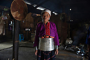 A young girl who is a member of a sub-group of the Palaung ethnic minority stands inside her family's communal house. The tribe is famous for the silver bands un-married girls wear around their waist, the number depending on the wealth of their family. Once they are married most are removed leaving only a few remaining.
