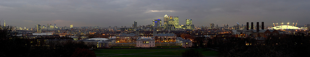 Greenwich Park, London. Sunset panorama view over the Maritime Museum, and University of Greenwich towards Canary Wharf, showing the 02 Dome.