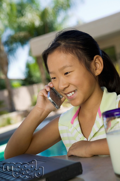 Young Girl sitting at backyard table Using Laptop and Cell Phone