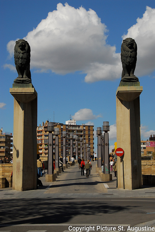 """Lions guard the entrance to the famous Puente de Piedra Bridge in Zaragoza, Spain. The stone bridge is built over the widest point of the river Ebro. A cross in the middle of the bridge is a tribute to The War of Independence and the pair of lions anchoring the end of the bridge represent the """"Lion"""" symbol of the city of Zaragoza. Zaragoza is in Aragon, Spain and is the location of Expo 2008. This Expo's focus is the  global sustainability of water."""