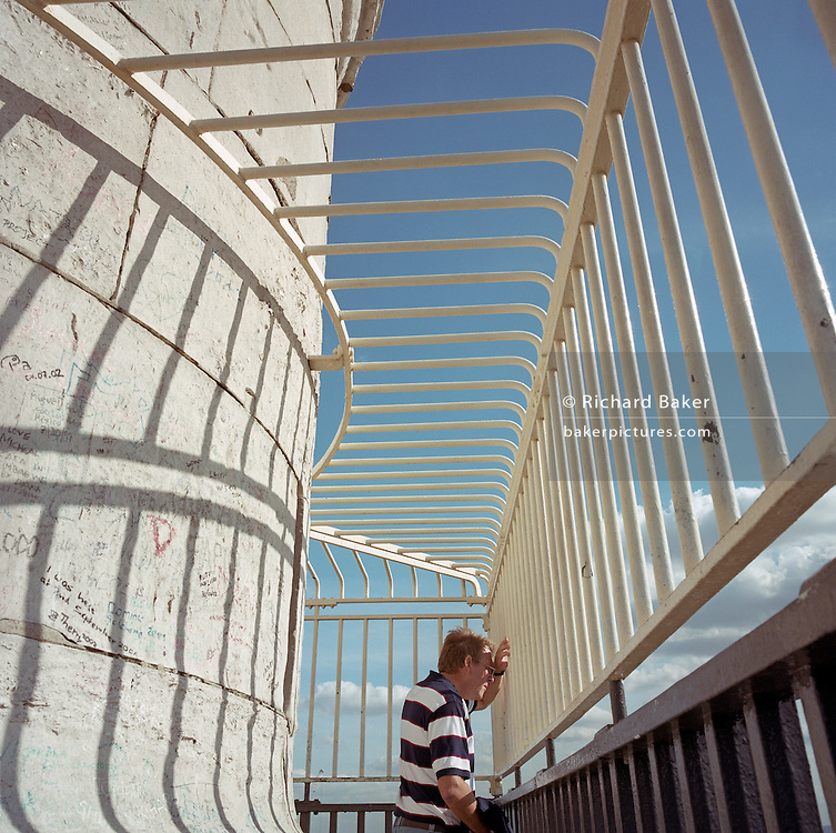 The stripes of a man's t-shirt are echoed in the bars of the Monument and their shadows on the column's surface.