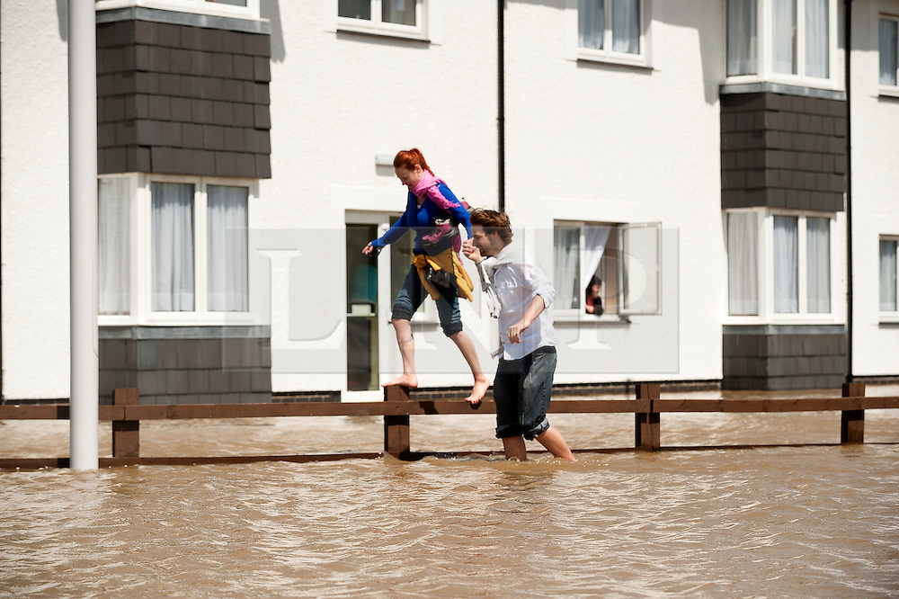 © Licensed to London News Pictures. 09/06/2012. London, UK. People wade throughout he floodwater. The River Rheidol, swollen after two days heavy rain, and with a high tide forcing the waters back, bursts its banks and floods low-lying areas of shops and houses on the outskirts of Aberystwyth Wales UK. Photo credit : Keith Morris/LNP