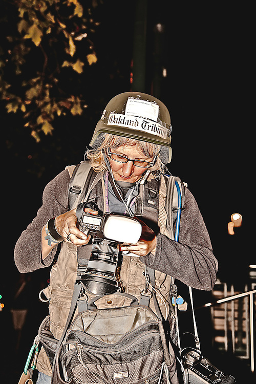 Prepared-for-anything Oakland Tribune photographer, covers Occupy Oakland movement in Oakland, CA.  Copyright 2011 Reid McNally.