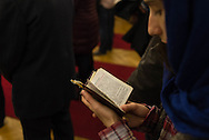 A young woman reads from a prayer book at a Greek Orthodox service in Warsaw, Poland