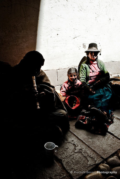 A Quechua family beg in an alleyway in Cusco, Peru