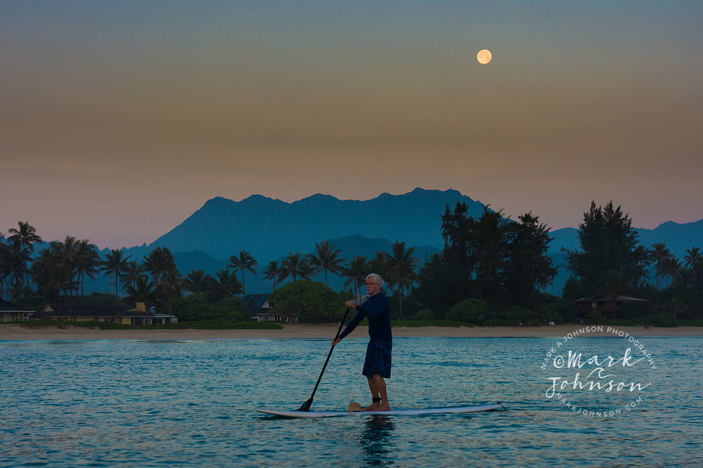 Stand-Up Paddle Boarder with full moon setting behind the Koolau Mountains as seen from Kailua Bay, Oahu, Hawaii