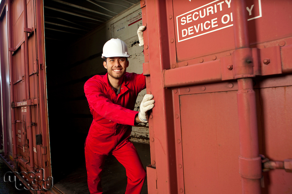 Hispanic worker opening industrial railway carriage