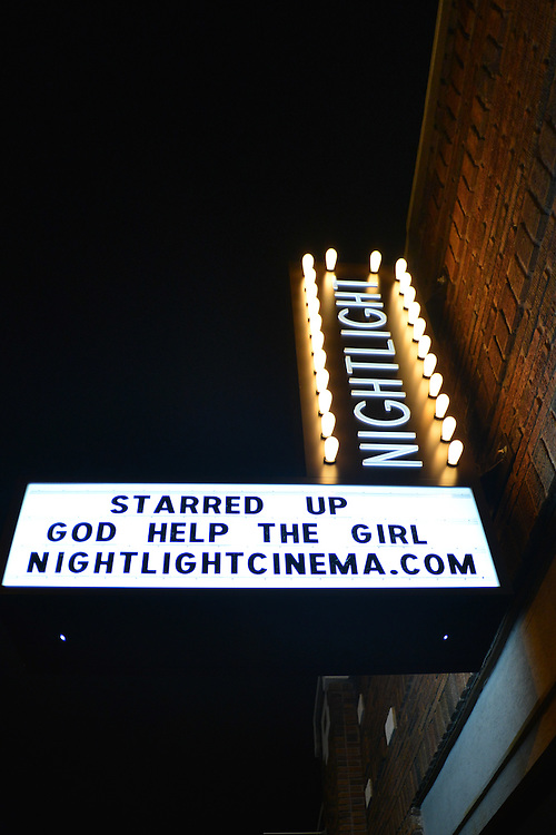Exterior of the lit sign for the Nightlight Cinema in the evening.