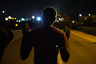 "A protester stands with his arms raised before a line of tactical police in Ferguson, Mo., on Wednesday, August 13, 2014. Moments before being shot and killed by police last weekend, Brown allegedly raised his hands in the air and said ""don't shoot."" Since then, ""Hands Up Don't Shoot"" has become a rallying cry among protesters. A peaceful gathering of protesters earlier in the day was marred after some protesters threw rocks and plastic bottles at police."