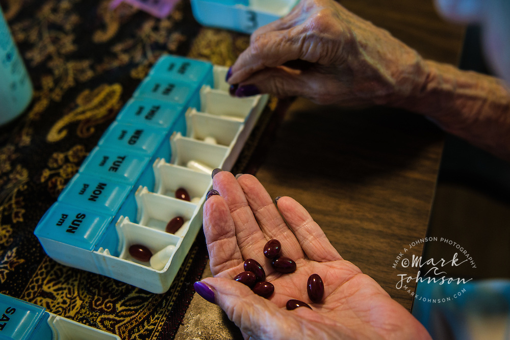 Closeup of an older woman's hands putting pills into weekly pill dispenser