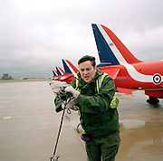 Engineering ground staff of the Red Arrows, Britain's RAF aerobatic team, coils up anti-static cable after refuelling a Hawk.