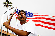 10 APRIL 2006 - PHOENIX, AZ: An immigrant waves an American flag at a rally in Phoenix, AZ. More than 200,000 people participated in a march for immigrants's rights in Phoenix Monday. The march was a part of a national day of action on behalf of undocumented immigrants. There were more than 100 such demonstrations across the US Monday. Protestors were encouraged to wear white, to symbolize peace, and wave American flags, to demonstrate their patriotism to the US.  Photo by Jack Kurtz