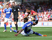 Josh Emmanuel scissor tackling Andy Gogia during the Sky Bet Championship match between Brentford and Ipswich Town at Griffin Park, London, England on 8 August 2015. Photo by Matthew Redman.