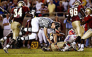 Football umpire Russ Pulley gets knocked over by Florida State's Ernie Sims #34 during a play in the game against the University of Florida on November 20, 2004.