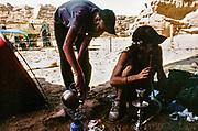 Two men boiling kettle and smoking from a hookah, East Tek, Wadi Rum, Jordan, 2008