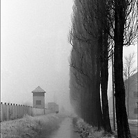 """Germany's first concentration camp viewed along a canal and row of trees in snow. Published in Jon Naar's """"Getting the Picture"""" in 2005.  Taken with a 35 mm Leica M4."""