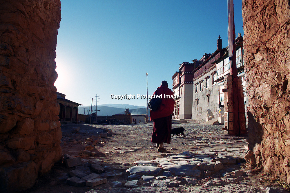 """ZHONGDIAN COUNTY, DECEMBER 19, 2000: a Tibetan monk walks through the gate of the Songzanlin monastery, Yunnan province , December 19, 2000..Zhongdian county is believed to be part of the areas on which James Hilton's famous novel """" lost Horizon""""- a description of Shangri-La- is modelled.. ."""