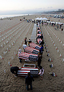 Volunteers carry empty coffins draped in American flags at 'Arlington West' in Santa Monica to honor the 3000th soldier killed in Iraq December 31, 2006. REUTERS/Max Morse (UNITED STATES)
