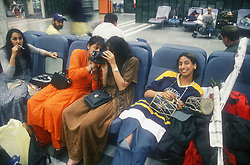 Tourists playing with video camera and sitting in airport departure lounge,