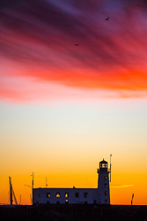 © Licensed to London News Pictures. 03/02/2019. Scarborough UK. The clouds above Scarborough lighthouse are turned red at Dawn this morning on the Yorkshire coast. Photo credit: Andrew McCaren/LNP