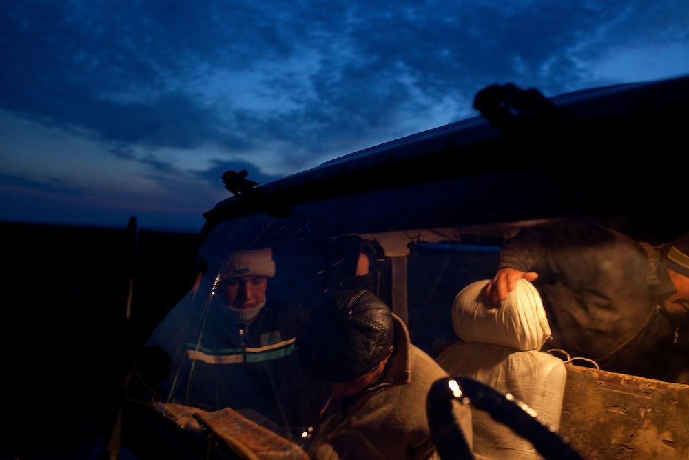CREDIT: DOMINIC BRACCO II..SLUG:PRJ/KAZAKHSTAN..DATE:11/1/2009..CAPTION:Fisherman Gaziz Yeleusizov, left, and fisherman Almat Aidoraliev, 21 of Aralsk (entering the back of the vehicle) get ready to go into down with the fish buyers so they can bathe and get a new set of clothes. The fishermen stay near the seashore for several months at a time because the sea has receded so far from their homes.  ..Aral Sea Overview: ..During the 1960s the USSR began irrigating the waters of the Aral Sea in southern Kazakhstan to combat their growing food crisis. The Soviets severely miscalculated and water began receding quickly from the port cities. The waters continued to recede. By 2000 the water was 80 km away from the city of Aralsk, a main seaport in Kazakhstan. In 2005 with help from the World Bank, construction began on a 13km dike that locals hoped would bring the waters back to their original shores. The project raised water quality and fishing was able to resume, however four years after completion of the dike the water is still 50km from Aralsk's port. Locals seem mixed on the possibility of the sea returning after more than 40 years without the sea. Fishermen from Aralsk make a three-hour path through soft desert road along the former seabed. The only source of income for many is cattle, horses, and camels, which have, began to overgraze the areas of the former seabed and surrounding desert. Because of this nutrient rich topsoil is lifted by the wind and the process of desertification continues.  .