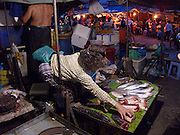 A woman shows off fresh fish at the night market.