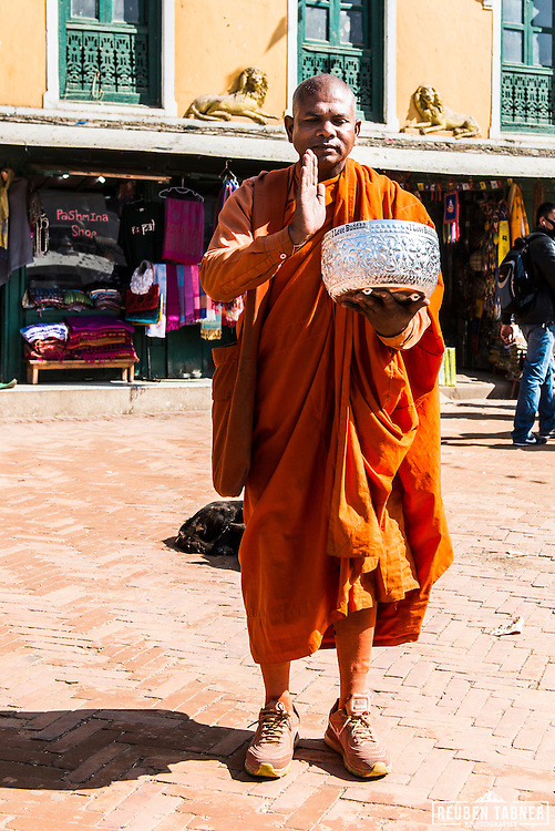 A monk stands next to the Boudhanath stupa in Kathmandu, Nepal.