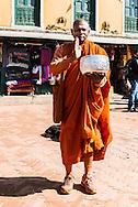 A monk stands next to the Boudhanath stupa in Kathmandu, Nepal.