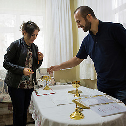 Father Adday, 34, prepares for mass at an apartment in Kirsehir, Turkey. <br /> Faten Somo lights incense next to him.<br /> Father Adday celebrated a mass in this apartment with about 30 people. There are no Catholic churches in this part of the country and when Father Adday visits the Eucharist is celebrated in homes.