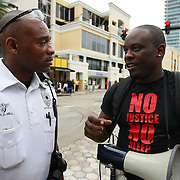 "Olumide Ajile speaks with an Orlando police officer before protesters march and hold signs in the No Justice No Peace- ""March Against Gun Violence""  walk from Lake Eola in downtown Orlando, to the Orange County Courthouse on Wednesday, July 17, 2013. The march was organized by the Modarres Law Firm and Orlando attorney Natalie Jackson, one of the attorneys for Trayvon Martins parents. (AP Photo/Alex Menendez)"