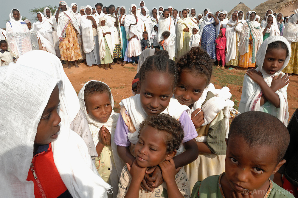 """Villagers pray on a normal Sunday service as Tiblits neighbor Zaid Tesheme, 31 has her baby baptized with the name Mihreteab inside Coptic St. Mary's chapel in the village of Fithi which means """"justice"""" on the outskirts of  Barentu, Eritrea August 27, 2006. During this ceremony, . The donkey that Tiblets received from the womens union """"Hamade"""", helped them prepare for the celebration afterward"""