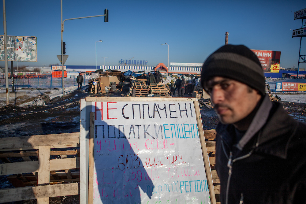 "A man passing the barrikades blockading a building supplies store named ""Epicenter"" in the city of Lviv, Ukraine."