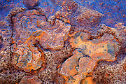 Close-up detail of oxidation and rust pitting on a cannon barrel at Fuengirola Castle or Sohail Castle.  The orange is caused by the oxidation of the iron (rust), while the blue is the reflection of a clear blue sky.  Castillo de Sohail was a 10th century Arab castle accupied by the Moors and later conquered and ruined by the Christian Monarchs in 1485.  Rebuilt by the French during the Peninsular War, and successfully defended from a British-Spanish force at the Battle of Fuengirola, 1810 by a band of 200 Polish soldiers.  Castle renovated in 1995.