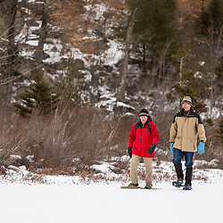Two men walk on Round Pond in winter. Barrington, New Hampshire.