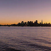 San Francisco California skyline and Oakland Bay Bridge view across San Francisco Bay from Treasure Island at sunset