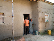 "Keru Imam (left), 27 and his wife Caada Jemam, 20, outside their new home in Zwei, Ethiopia. They have raised the money to pay for the new house by selling seedlings to larger farms in the area...Before Keru and his wife became involved in SEDA, an organisation working with Send a Cow, they didn't grow any fruit or vegetables and all they used to eat maize. As a result they used to get ill a lot. He now finds he has a lot more energy to work on the farm. During times of droughts he used to be forced to work as a labourer being paid 1 or 2 Birr a day, now he is starting to employee other people as labourers...""I am not afraid of drought because of what i have learnt."""