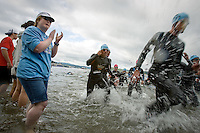 JEROME A. POLLOS/Press..Wendy Ozminkowski encourages swimmers exiting Lake Coeur d'Alene to start the second lap of the 2.4-mile swim Sunday during the Ford Ironman Coeur d'Alene.