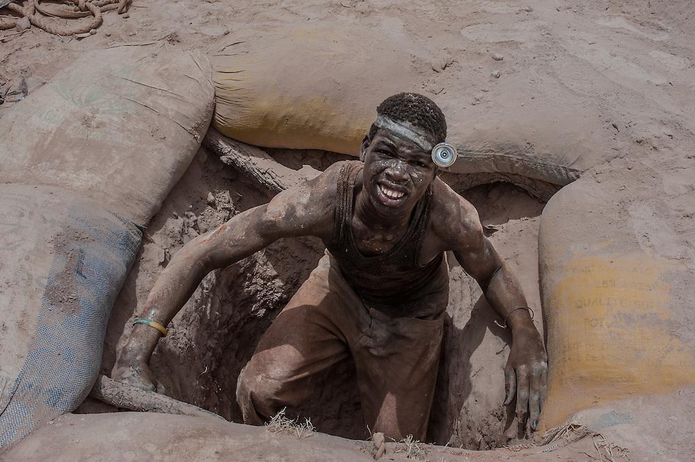 Yameogo Salifu, 21 anni, riappare in superficie dopo aver lavorato in una galleria profonda 25 metri nella miniera d'oro artigianale di Nobsin in Burkina Faso il 13 Maggio 2014.  Nel villaggio dove &egrave; nato, a 31 km dalla miniera, faceva il contadino ma  Dice &ldquo;Ho iniziato a cercare oro 6 mesi fa. Li sotto &egrave; buio pesto e fa caldissimo. &quot;Ma non ho paura.&quot; &ldquo;La sopravvivenza &egrave; pi&ugrave; importante della paura.&rdquo; <br /> &ldquo;Ricevo dal proprietario della galleria una percentuale sulla vendita dell&rsquo;oro che ho trovato&rdquo; continua. &ldquo;Qualche giorno 5000 CFA, se va bene 10000 CFA. Spesso niente. Tutto dipende dalla fortuna e dalla qualit&agrave; della vena mineraria&rdquo;