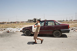 © Licensed to London News Pictures. Hamdaniyah, Iraq. 26/07/2014. A young Iraqi Christian refugee from Mosul hauls a water container from a tanker provided by Kurdish Zeravani soldiers in Hamdaniyah, Iraq.<br /> <br /> <br /> Having taken over Mosul Iraq's second largest city in June 2014, fighter of the Islamic State (formerly known as ISIS) have systematically expelled the cities Christian population. Despite having been present in the city for more than 1600 years, Christians in the city were given just days to either convert to Islam, pay a tax for being Christian or leave; many of those that left were also robbed at gunpoint as they passed through Islamic State checkpoints.. Photo credit : Matt Cetti-Roberts/LNP