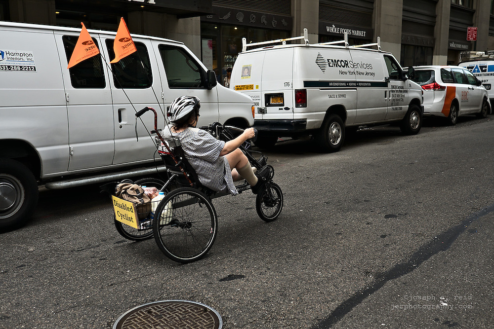Woman riding recumbent tricycle, New York, NY, US