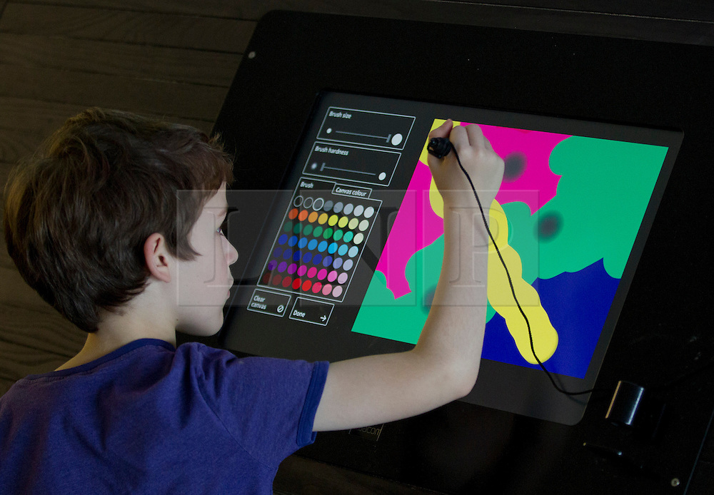 © Licensed to London News Pictures. 19/09/2013. London, UK. Ivo Burton-Franklin (10) uses a touch screen to draw art at the press launch of 'Make Your Mark on Tate Modern' at the gallery in London today (19/09/2013). The new interactive feature allows artists and members of the public to create art and then post it to the on one of the 75 display screens, the created art is then archived by the gallery. Photo credit: Matt Cetti-Roberts/LNP