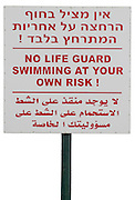 Israel, sea of Galilee, No life guard Swimming at your own risk sign in Hebrew English and Arabic a cut out