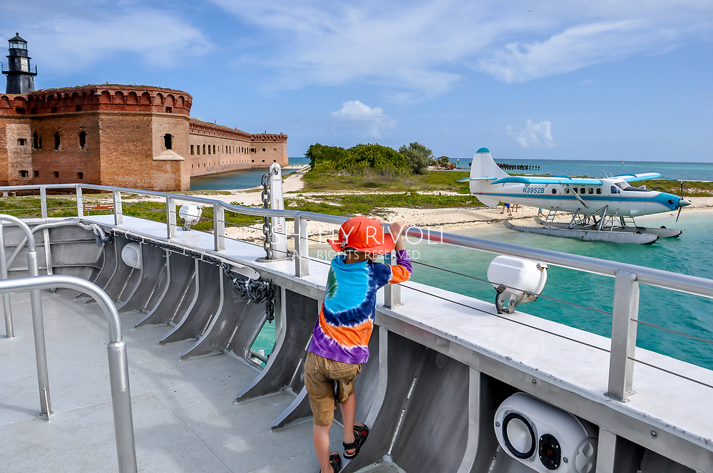 A child arrives at Dry Tortugas National Park, viewing a sea plane from the ferry boat with turquoise water and Fort Jefferson in the background.The boy wears colorful clothing including a sun hat and tie-dye shirt. Model released photo.