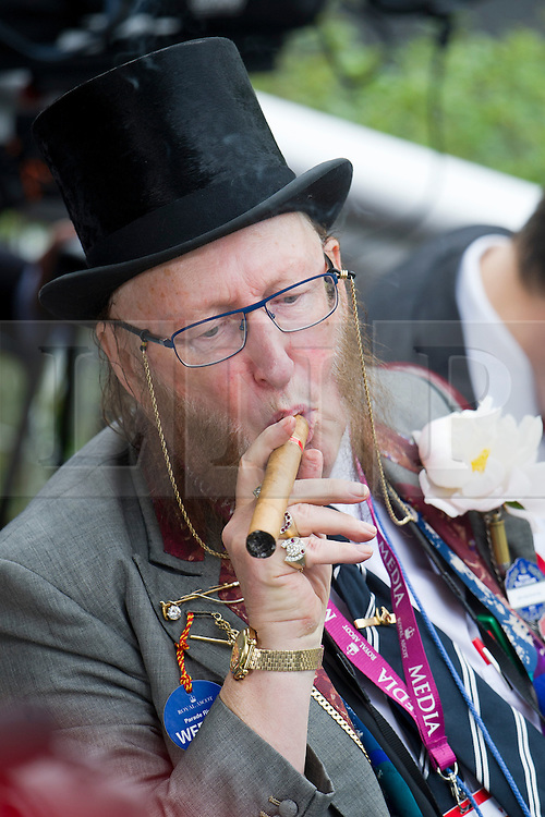 © London News Pictures. 18/06/2013. Ascot, UK.  Tv commentator John McCririck smoking a cigar on day one of Royal Ascot at Ascot racecourse in Berkshire, on June 18, 2013.  The 5 day showcase event,  which is one of the highlights of the racing calendar, has been held at the famous Berkshire course since 1711 and tradition is a hallmark of the meeting. Top hats and tails remain compulsory in parts of the course. Photo credit should read: Ben Cawthra/LNP